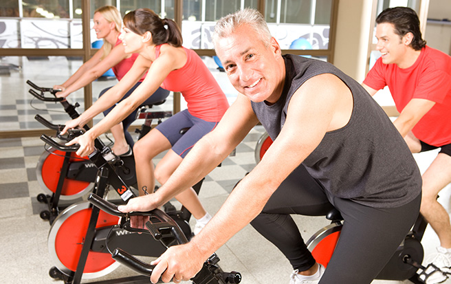 spinning class with man smiling at camera