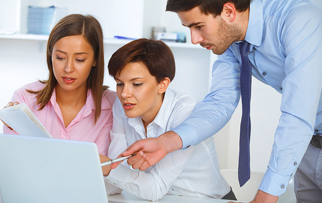 business professionals looking at laptop computer