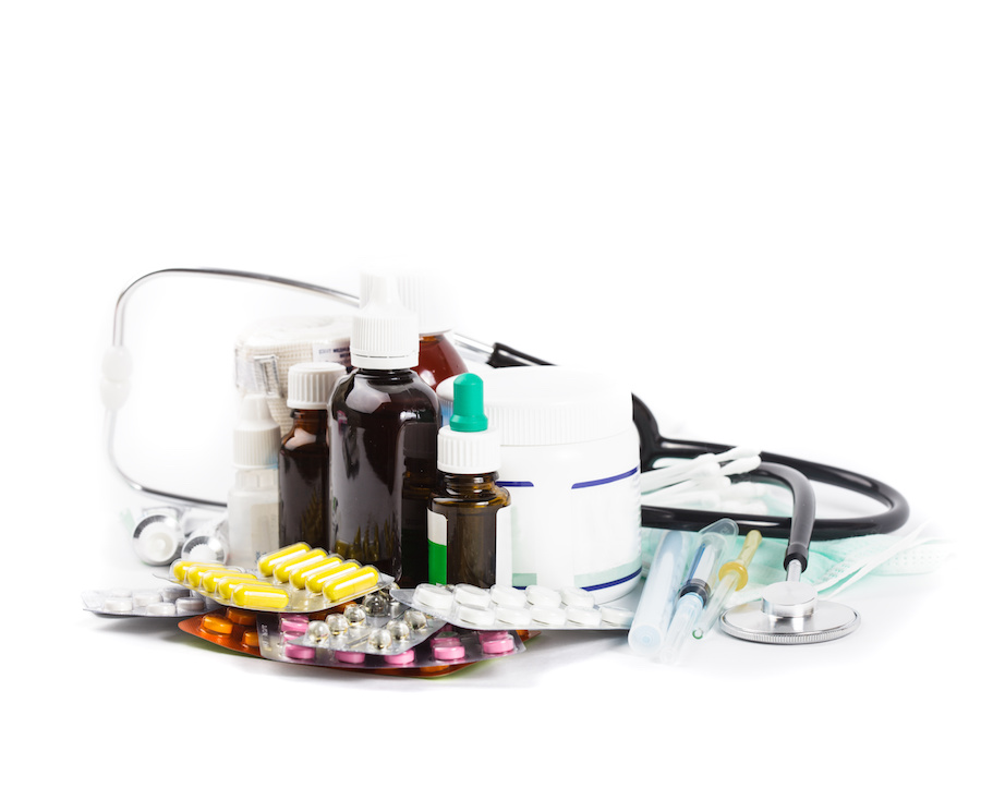 A variety of medicine and stethoscope on white background