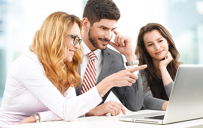group of business professionals around the computer
