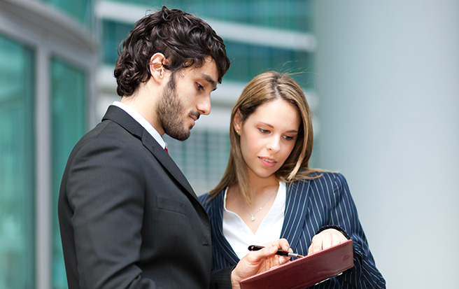man and woman looking at clipboard