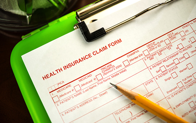 health insurance claim form on clipboard with pencil