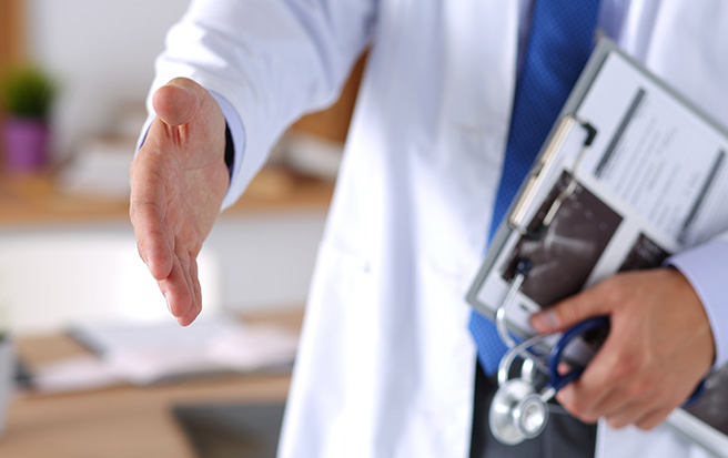 physician with clipboard reaching out his hand to shake